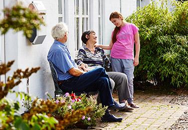 En familie taler lykkeligt sammen. Forældrene sidder på en bænk med deres datter stående med hånden på mødres skulder