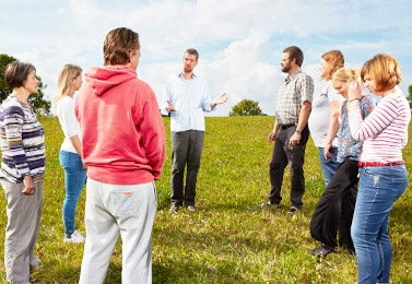 Carl plesner teaches NVC to a group of people standing in a circle in a field